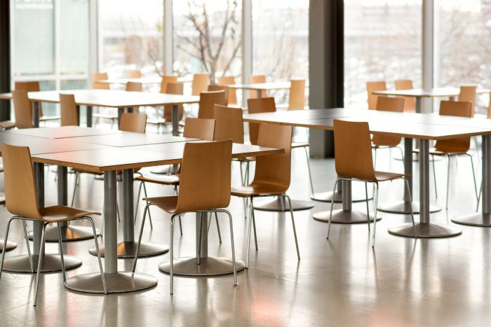 Interior of an empty canteen with modern tables and chairs lit by daylight through large view windows