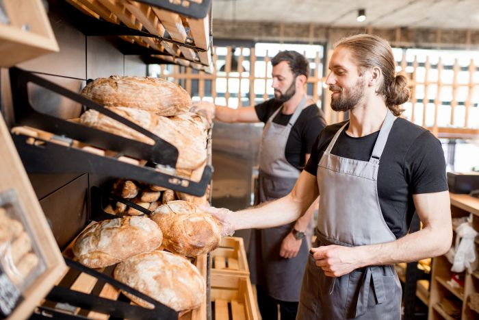 Handsome sellers putting bread loafs on the shelves of the bakery shop